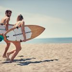 Young happy man and woman surfers running together to surf at the beach