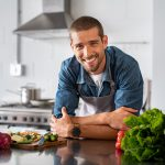 Handsome young man leaning on kitchen counter with vegetables and looking at camera. Smiling man wearing apron while preparing food at home. Portrait of happy casual guy leaning on steel counter in the kitchen with vegetables and ingredients on it.